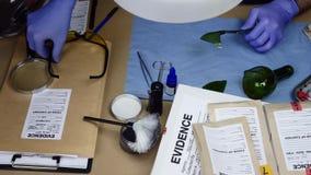 Vetenskapligt skivat undersöka för polis spårar av kristall av en flaska i ballistiskt laboratorium arkivfilmer