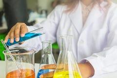 Vetenskapsexperiment kemister som har diskussion i labb Vetenskapsassistent som arbetar i den kemiska labbet arkivbild