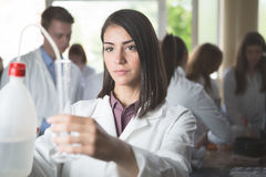 Vetenskapsstudenter som arbetar med kemikalieer i labbet på universitetet Lycklig student, innehåll för experimentella resultat arkivfoton