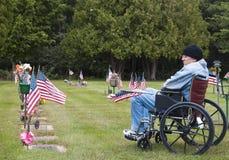 Veteraan in een rolstoel bij de begraafplaats Stock Foto