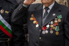 A veteran decorated with medals and orders on the costume gives honor during a parade. royalty free stock photos