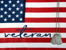 Veteran dog tags on American flag. Word veteran and military dog tags on American flag background royalty free stock images