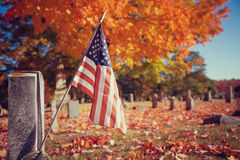 Veteran flag in autumn cemetery. American veteran flag in autumn cemetery. Vintage filter effects royalty free stock photography