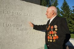 Elderly man with orders and medals. A veteran of the Great Patriotic War against the inscription `Eternal glory to the heroes! Be worthy in memory of the fallen stock photo