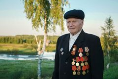 Veteran of the Great Patriotic War. A veteran of the Great Patriotic War stands in the background of a peaceful landscape royalty free stock photos