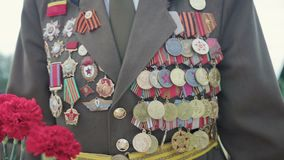 Veteran of the great Patriotic war and world war II in uniform with many badges and orders comes with red flowers. Close