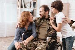 Veteran i en rullstol kom tillbaka från armén En man i likformig i en rullstol med hans familj Fotografering för Bildbyråer