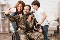 Veteran i en rullstol kom tillbaka från armén En man i likformig i en rullstol med hans familj Royaltyfria Bilder