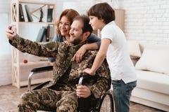 Veteran i en rullstol kom tillbaka från armén En man i likformig i en rullstol med hans familj royaltyfria foton
