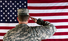 Veteran male solider saluting the flag of USA. Male Veteran soldier, back to camera, saluting United States of America flag Royalty Free Stock Photos