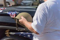 Veteran med USA-flaggan och WWI-hjälmen ståtar på Royaltyfri Bild