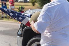 Veteran med USA-flaggan och WWI-hjälmen ståtar på Royaltyfria Bilder