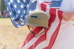 Veteran med USA-flaggan och WWI-hjälmen ståtar på Royaltyfri Fotografi