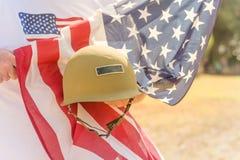 Veteran med USA-flaggan och WWI-hjälmen ståtar på Arkivbild