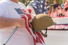Veteran med USA-flaggan och WWI-hjälmen ståtar på Arkivfoton