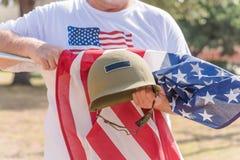 Veteran med USA-flaggan och WWI-hjälmen ståtar på Arkivbilder