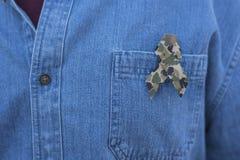 Veteran memorial ribbon. Person with simple denim shirt donning a veteran memorial ribbon with camouflage pattern Stock Images