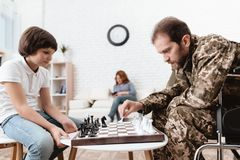 Veteran in military uniform in a wheelchair. A disabled man plays with his son in chess. Veteran in military uniform in a wheelchair. A disabled men plays with Royalty Free Stock Photos