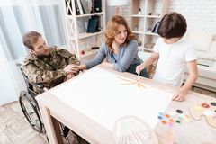 A veteran in military uniform in a wheelchair spends time with his family. The boy draws with a brush. Stock Photo