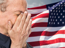 Veteran. Portrait of an elderly man with face closed by hand on USA flag background stock photography