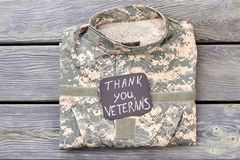 Veteran`s camo jacket, top view. Thank you veterans, wooden background stock image