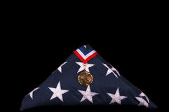 Veteran's Casket Flag And Medal. Folded US flag from veteran's casket and medal, black isolation Royalty Free Stock Photography