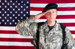 Veteran solider saluting with USA flag in background while armed. Veteran soldier, facing forward, saluting with USA flag in background. Soldier armed with Royalty Free Stock Images