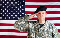 Veteran solider saluting with USA flag in background. Veteran soldier, facing forward, saluting with USA flag in background Royalty Free Stock Images