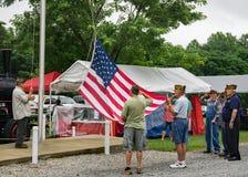 Veteran som lyfter amerikanska flaggan royaltyfria foton