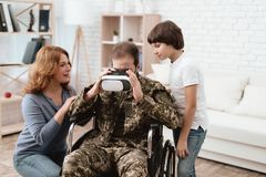 The veteran in a wheelchair came back from the army. A man in uniform in a wheelchair with his family. Man in wheelchair returned from army. A men looks into stock photography