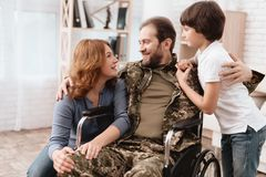 The veteran in a wheelchair came back from the army. A man in uniform in a wheelchair with his family. The veteran in a wheelchair came back from the army. Wife stock image
