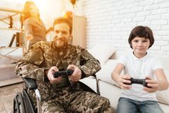 The veteran in a wheelchair came back from the army. A man in uniform in a wheelchair with his family. Stock Photo