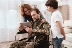 The veteran in a wheelchair came back from the army. A man in uniform in a wheelchair with his family. The veteran in a wheelchair came back from the army. A Royalty Free Stock Photos