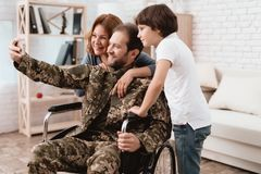 The veteran in a wheelchair came back from the army. A man in uniform in a wheelchair with his family. The veteran in a wheelchair came back from the army. Wife royalty free stock photos