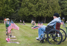 Veteran in a wheelchair at the cemetary. Disabled veteran in a wheelchair at the cemetery remembering his fallen brothers stock photo