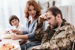 A veteran in a wheelchair dines with his family. A man in uniform is sitting at the kitchen table. Royalty Free Stock Image
