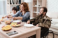 A veteran in a wheelchair dines with his family. A man in uniform is sitting at the kitchen table Royalty Free Stock Photography