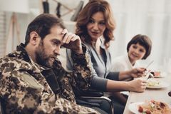 A Veteran In A Wheelchair Dinner With Family. Meeting Concept. Son And Wife. Camouflage Uniform. Resting Together. Feelings Showing. Patriotic Comeback Royalty Free Stock Photo