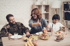 A Veteran In A Wheelchair Dinner With Family. Meeting Concept. Son And Wife. Camouflage Uniform. Resting Together. Feelings Showing. Patriotic Comeback Royalty Free Stock Image