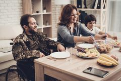 A Veteran In A Wheelchair Dinner With Family. Meeting Concept. Son And Wife. Camouflage Uniform. Resting Together. Feelings Showing. Patriotic Comeback Stock Images