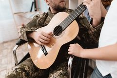 A veteran in a wheelchair is playing the guitar. Close-up photo of guitar and hands. Stock Photos