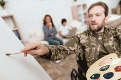 Veteran in wheelchair returned from army. Man in a wheelchair draws. Man hold paint and brush. Stock Photos