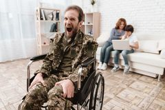 Veteran in wheelchair returned from army. Man in a wheelchair is in pain. He`s in military uniform. Stock Photo
