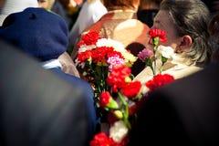 Veterane geben Blumen zum Tag des Sieges am 9. Mai Lizenzfreies Stockfoto