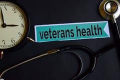 Veteranengezondheid op het drukdocument met de Inspiratie van het Gezondheidszorgconcept wekker, Zwarte stethoscoop stock afbeeldingen
