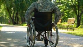 Veterano de guerra en la silla de ruedas que se mueve lentamente a lo largo del parque, defensor del país del héroe almacen de metraje de vídeo