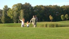 Veterano de los E.E.U.U. en camoubackgrounde con caminar de la familia ausente almacen de metraje de vídeo