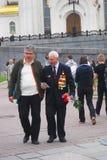 Veterano di guerra anziano che cammina con i fiori Fotografie Stock