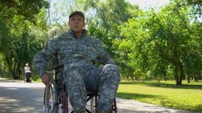 Veterano militar americano que mueve encendido la silla de ruedas en el parque de la ciudad, programa de la atención sanitaria almacen de video