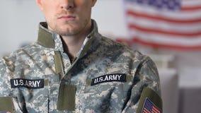Veterano militar valiente en el uniforme con las rayas, bandera del camuflaje en fondo almacen de metraje de vídeo